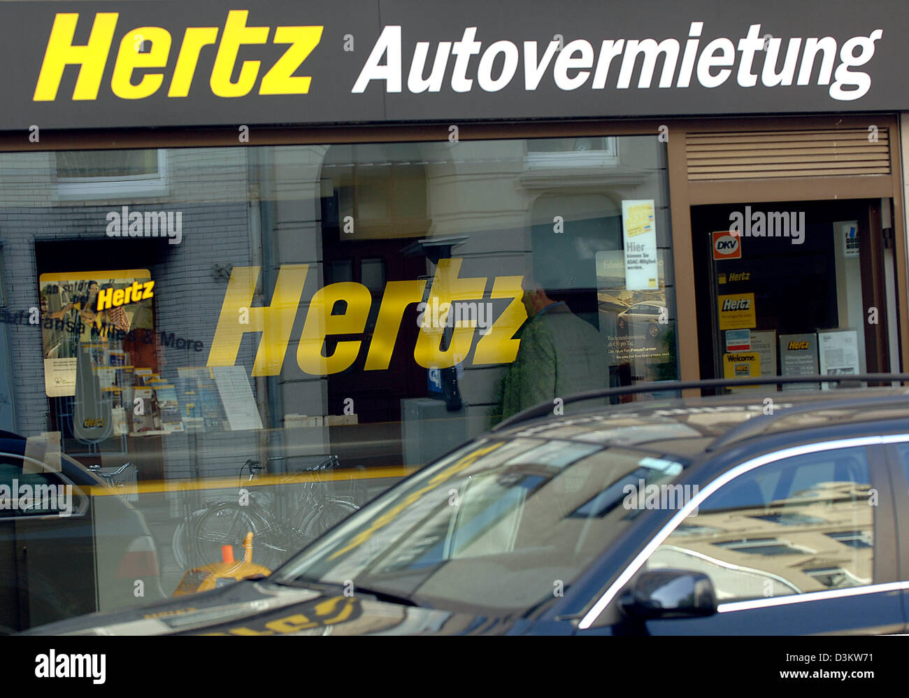 087ee6b957 (dpa) - A car drives past a branch of car rental agency Hertz in Cologne
