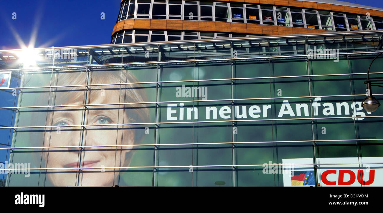 (dpa) - The sun rises and mirrors on the facade of the headquarter of the Christian Democratic Party (CDU) in Berlin, 18 September 2005. The poster attached to the facade features a portrait of Angela Merkel, chairwoman of the CDU and chancellor candidate. Supporters and journalists are going to follow the election results of the 2005 German Bundestag election at the  party headqua Stock Photo
