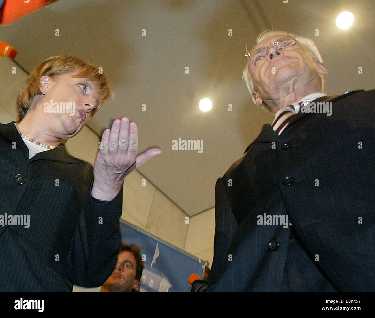 (dpa) - Angela Merkel (R), Chairwoman of the CDU and chancellor candidate, stands in front of Michael Glos, Head of the Bavarian CSU, talk to each other after the recent sessions of the new elected parliamentary faction of the CDU/CSU in Berlin, Tuesday, 20 September 2005. Despite the week results in the general election for the German Bundestag, Merkel was re-elected by her party  Stock Photo