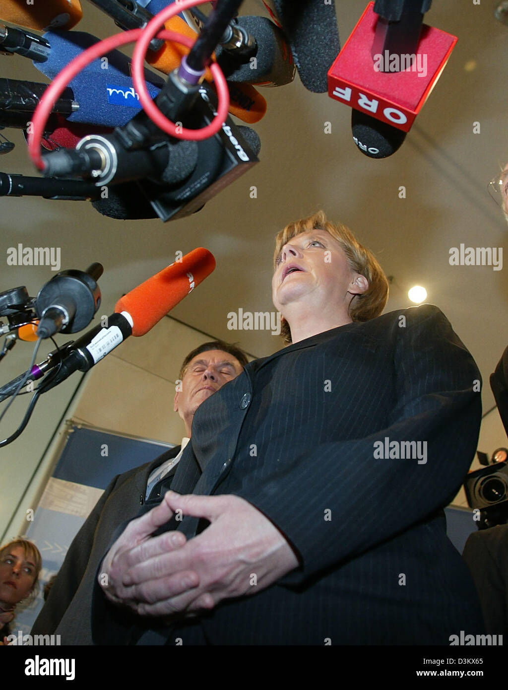 (dpa) - Angela Merkel (front), Chairwoman of the CDU and chancellor candidate, stands next to Michael Glos, Head of the Bavarian CSU, as she speaks during a short press conference after the session of the new elected parliamentary faction of the CDU/CSU in Berlin, Tuesday, 20 September 2005. Despite the week results in the general election for the German Bundestag, Merkel was re-el Stock Photo