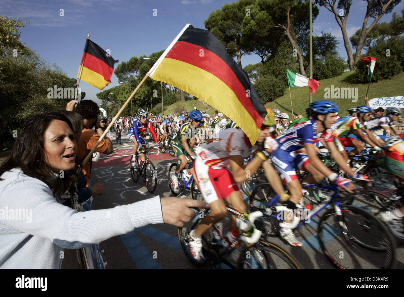dpa) - German cycling fans wave flags for the passing peloton during