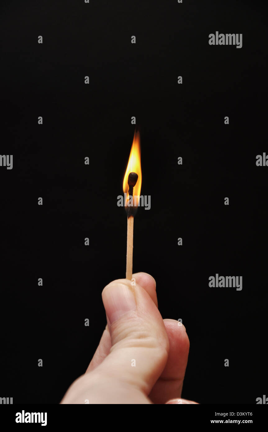 Fingers holding a lit match - Stock Image