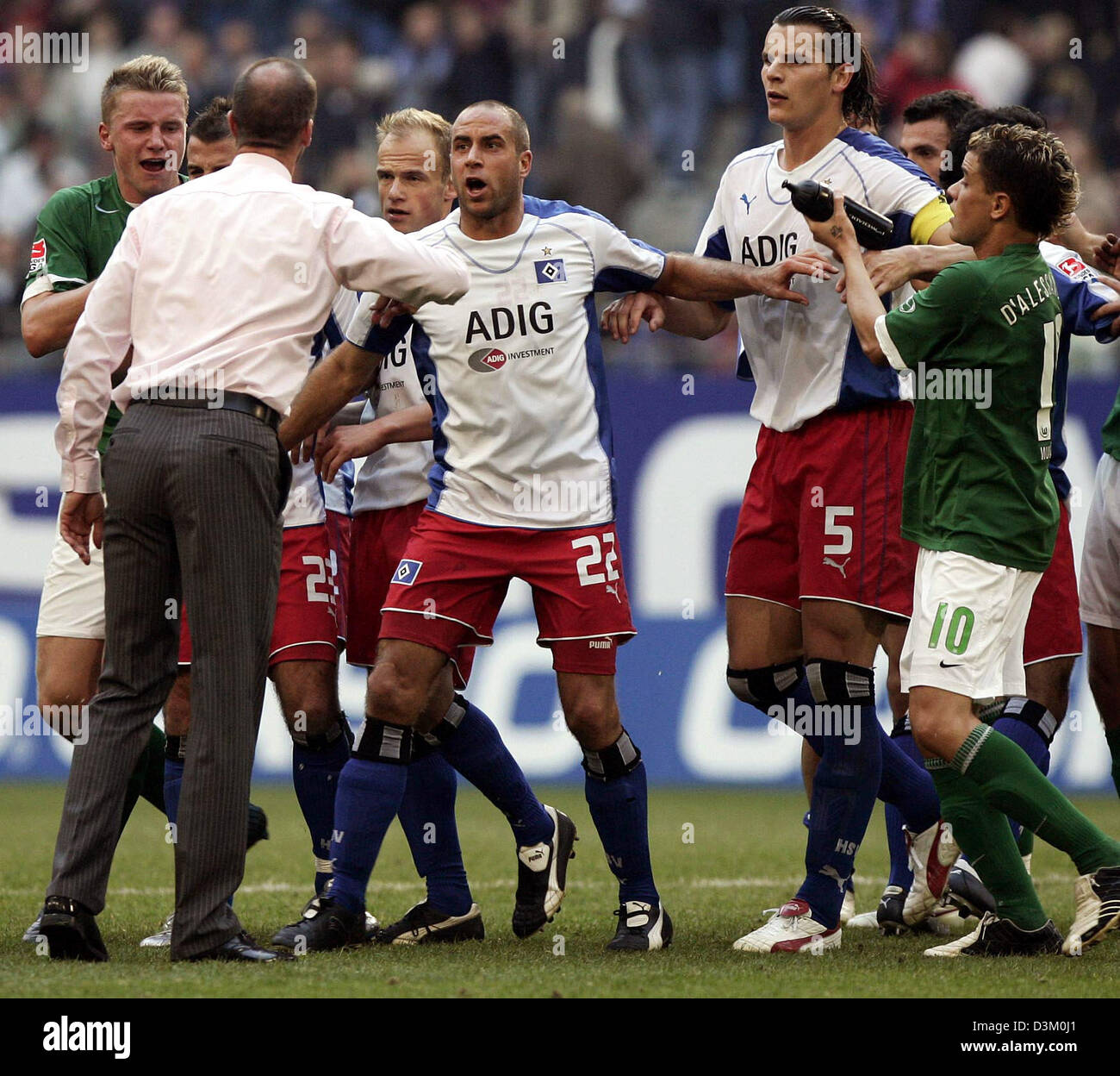 (dpa) - Coach of Wolfsburg Holger Fach (2nd L) and Rafael van der Vaart (B) of Hamburg argue with each other after Stock Photo