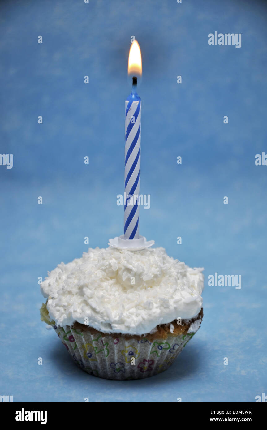 Vanilla cupcake with lit candle on top - Stock Image