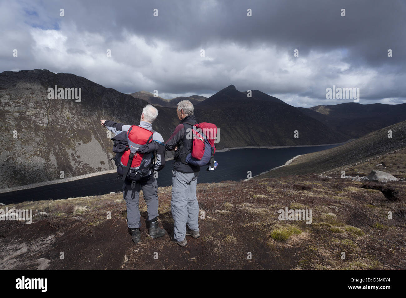 Two walkers looking across Ben Crom Reservoir from the slopes of Slieve Lamagan. Mourne Mountains, County Down, - Stock Image