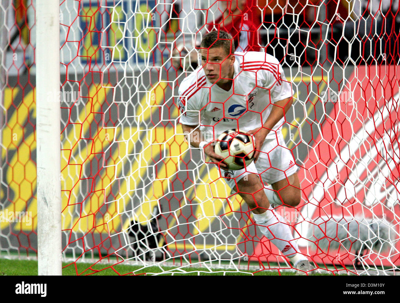 (dpa) - German international Lukas Podolski of Cologne fetches the ball after his team mate Albert Streit scored - Stock Image