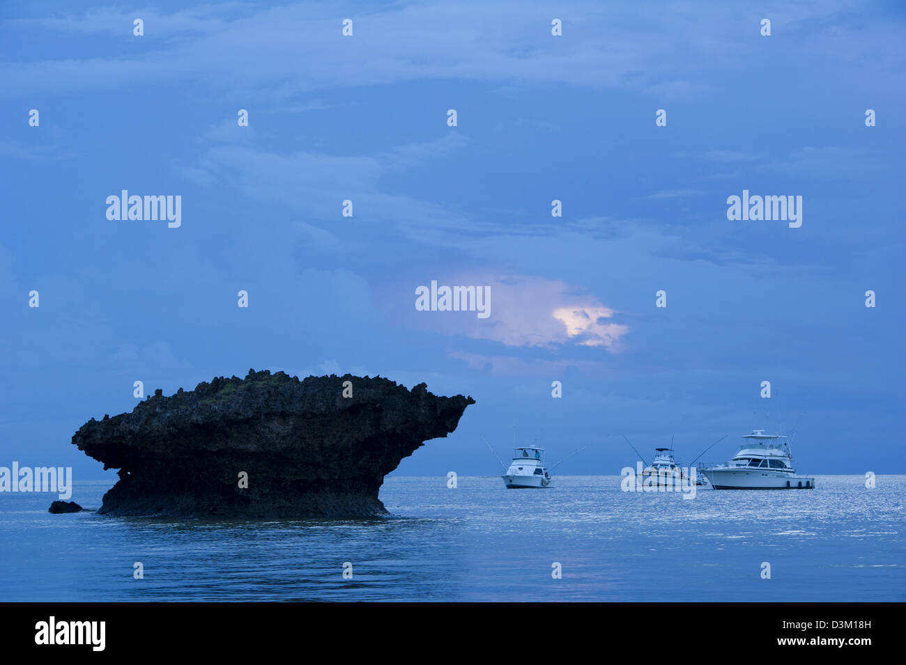 Fishing boats next to a coral outcrop at sunrise, Turtle Bay, Watamu, Kenya - Stock Image