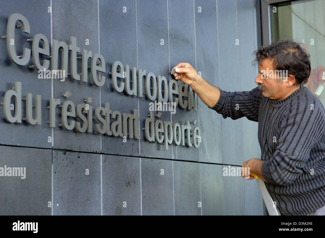 (dpa) - A worker completes the writing at the entrance of the memorial site 'European centre of the deported - Stock Image