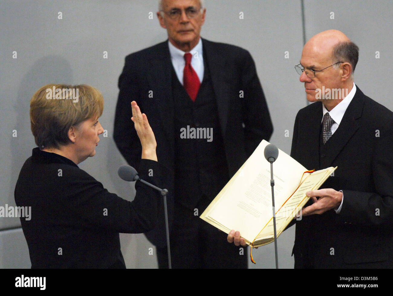 (dpa) - New elect German Chancellor Angela Merkel (L) takes the oath of office to President of the Bundestag, Norbert Lammert (R), as Wolfgang Zeh, director of the Bundestag looks on in Berlin, Germany, Tuesday 22 November 2005. Merkel of the conservative Christian Democratic Union (CDU) was elected with the majority votes of the parliament confirming her as the first female chance Stock Photo