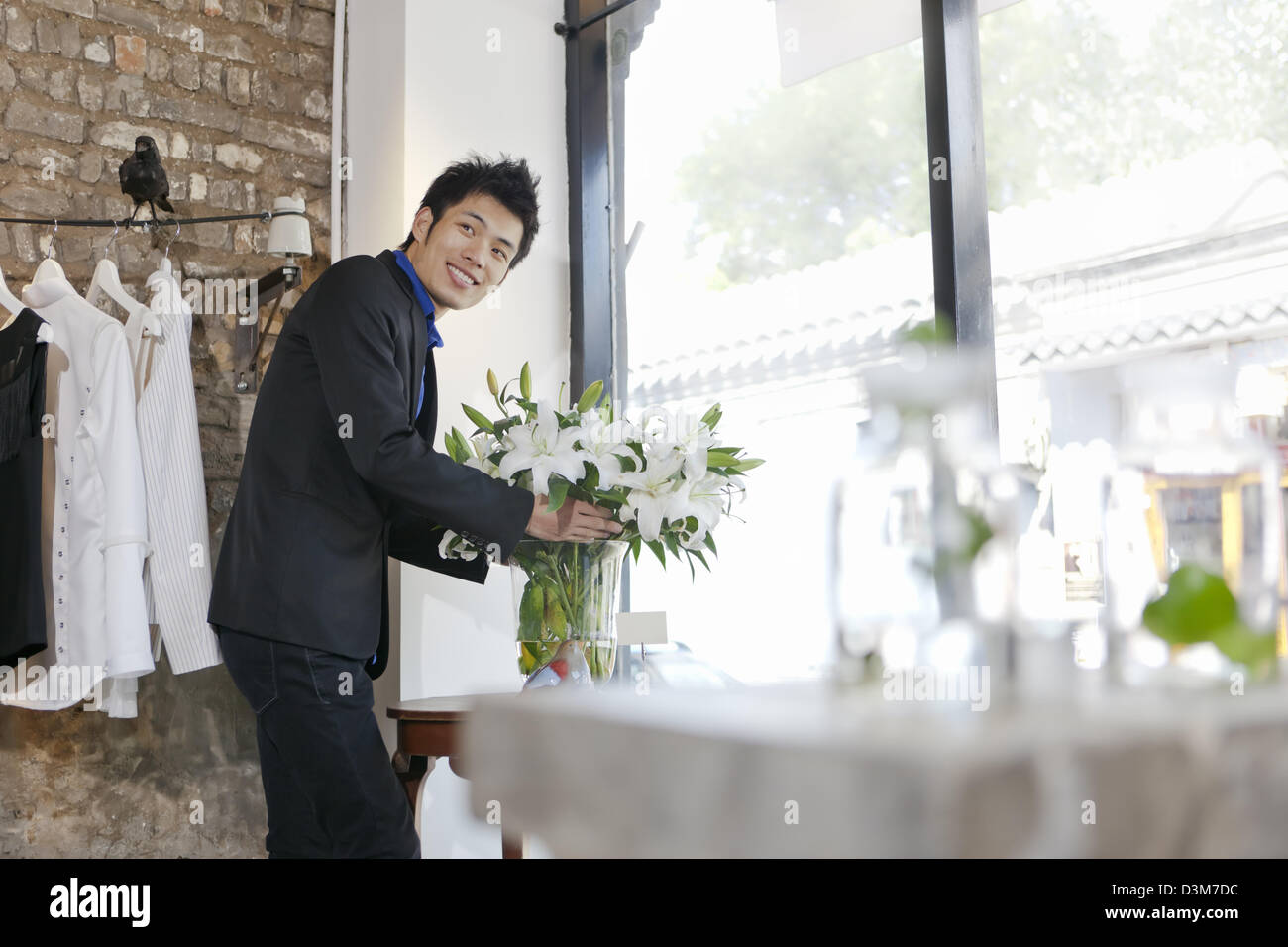 New generation Chinese entrepreneur, arranging floral decoration in a shop in trendy district of Dong Cheng in Beijing - Stock Image