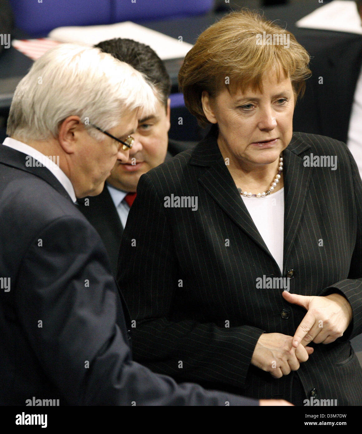 (dpa) - German Chancellor Angela Merkel (CDU) (R) and Foreign Minister Frank-Walter Steinmeier (SPD) (L) talk to each other during a parliamentary debate at the German lower house of parliament Bundestag in Berlin, on Wednesday, 14 December 2005. In the background German Environment Minister Sigmar Gabriel (SPD). Germany played no part in the US abduction of a German citizen who wa Stock Photo