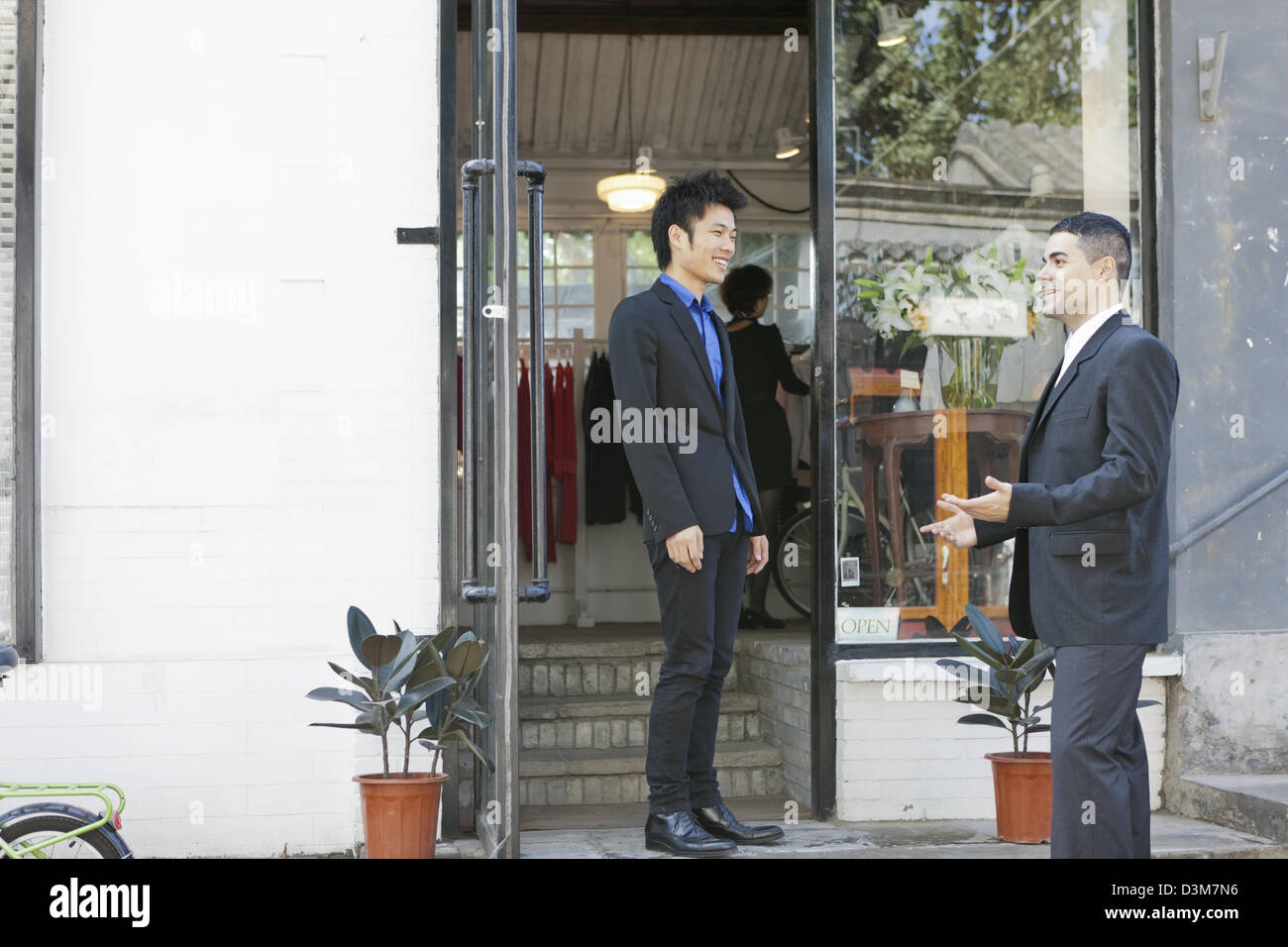 New generation Chinese entrepreneur, chatting with a customer in a shop in trendy district of Dong Cheng in Beijing - Stock Image