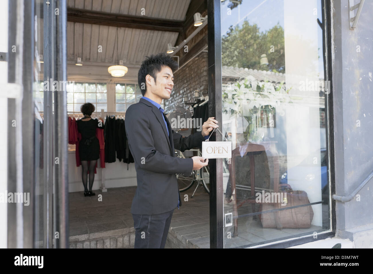 "New generation Chinese entrepreneur, putting up ""open' sign at the door of his shop in trendy district of Dong Cheng Stock Photo"