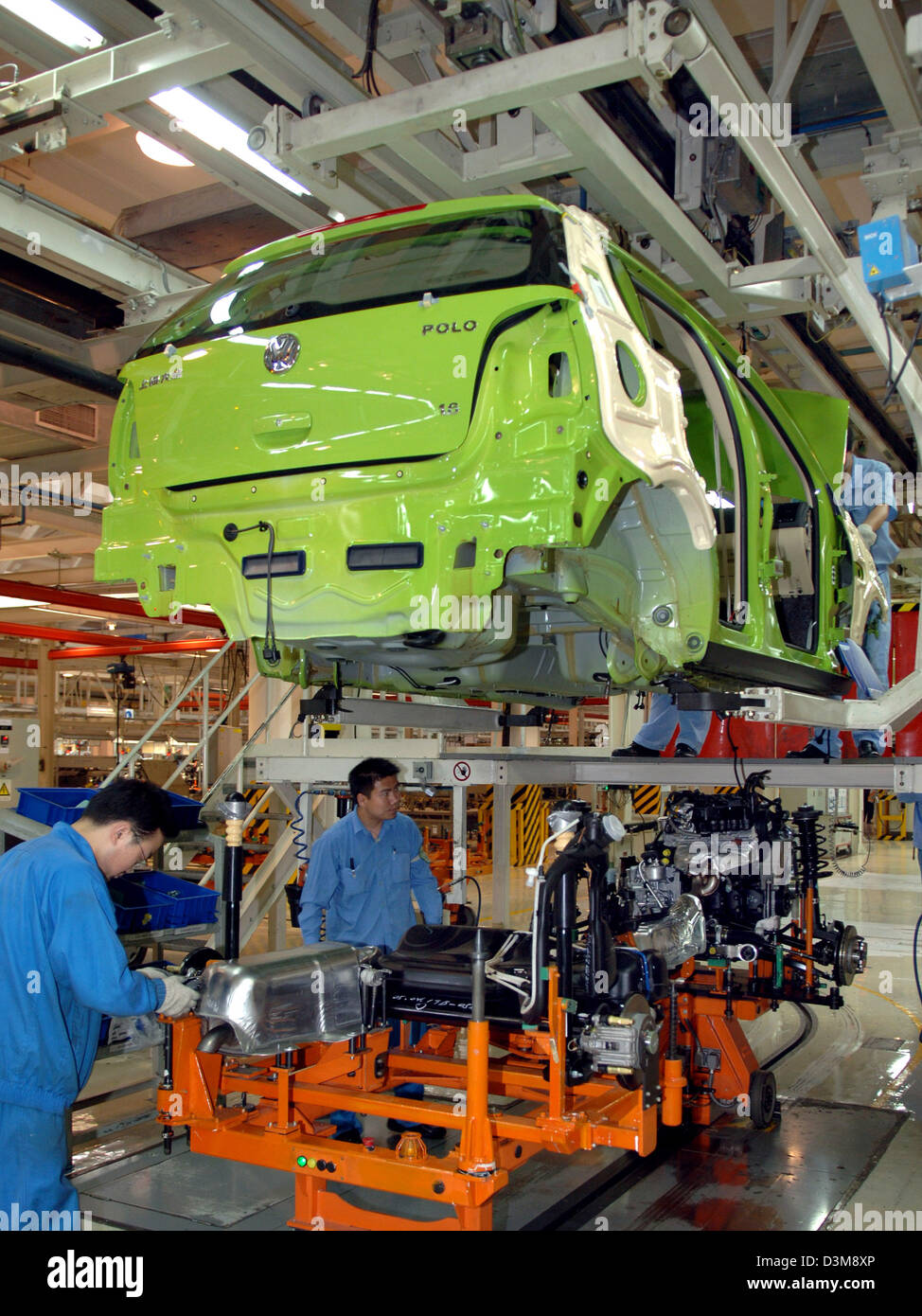 (dpa) - Chinese employees of Volkswagen (VW) assemble the car body with motor, axes and gear unit of a VW Polo on - Stock Image