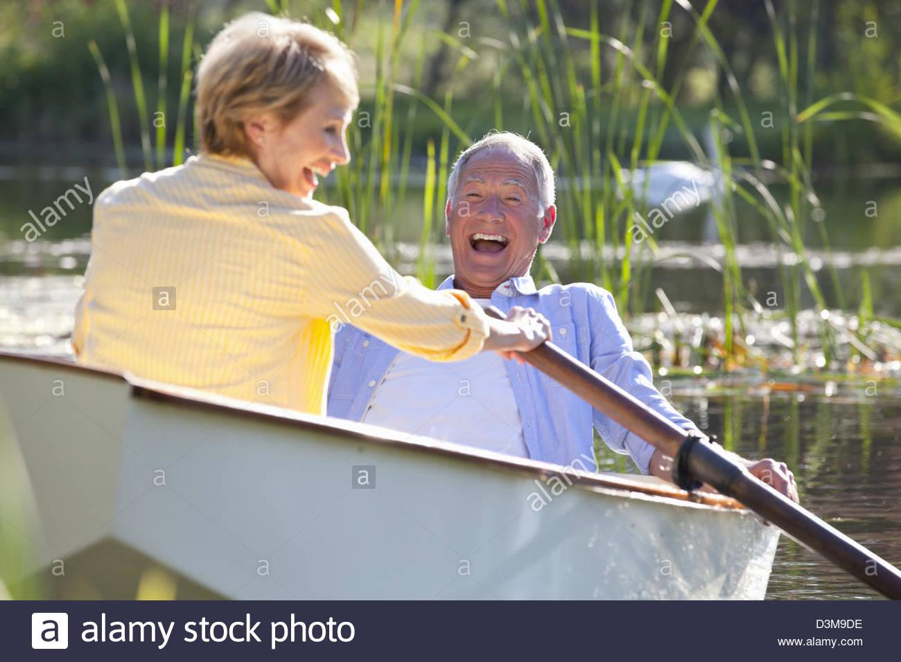 Smiling couple in rowboat on lake - Stock Image