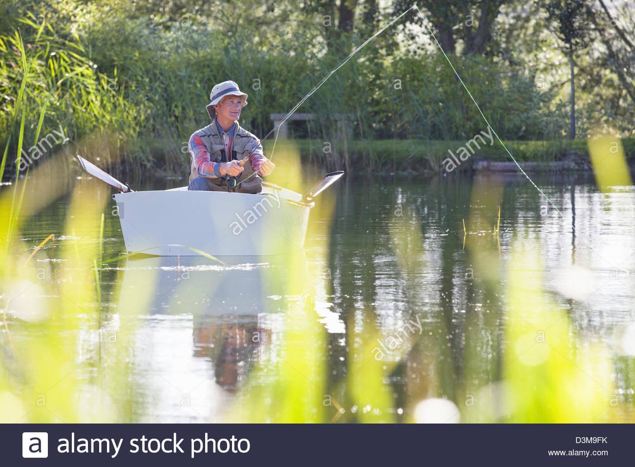 Man fishing from rowboat on lake - Stock Image