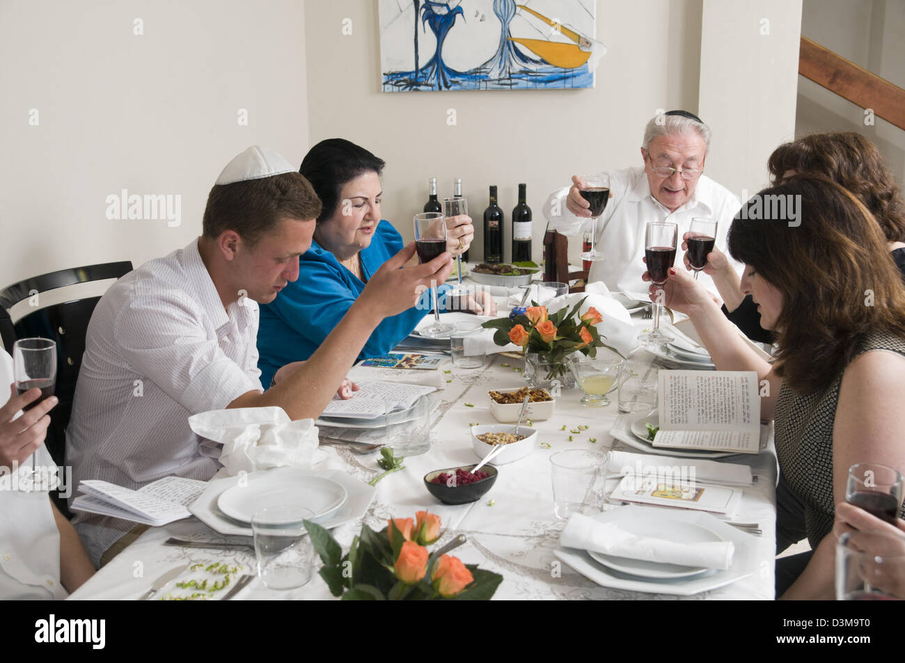 family sitting around a table set for a Jewish Festive meal on Passover (transliterated as Pesach or Pesah) - Stock Image