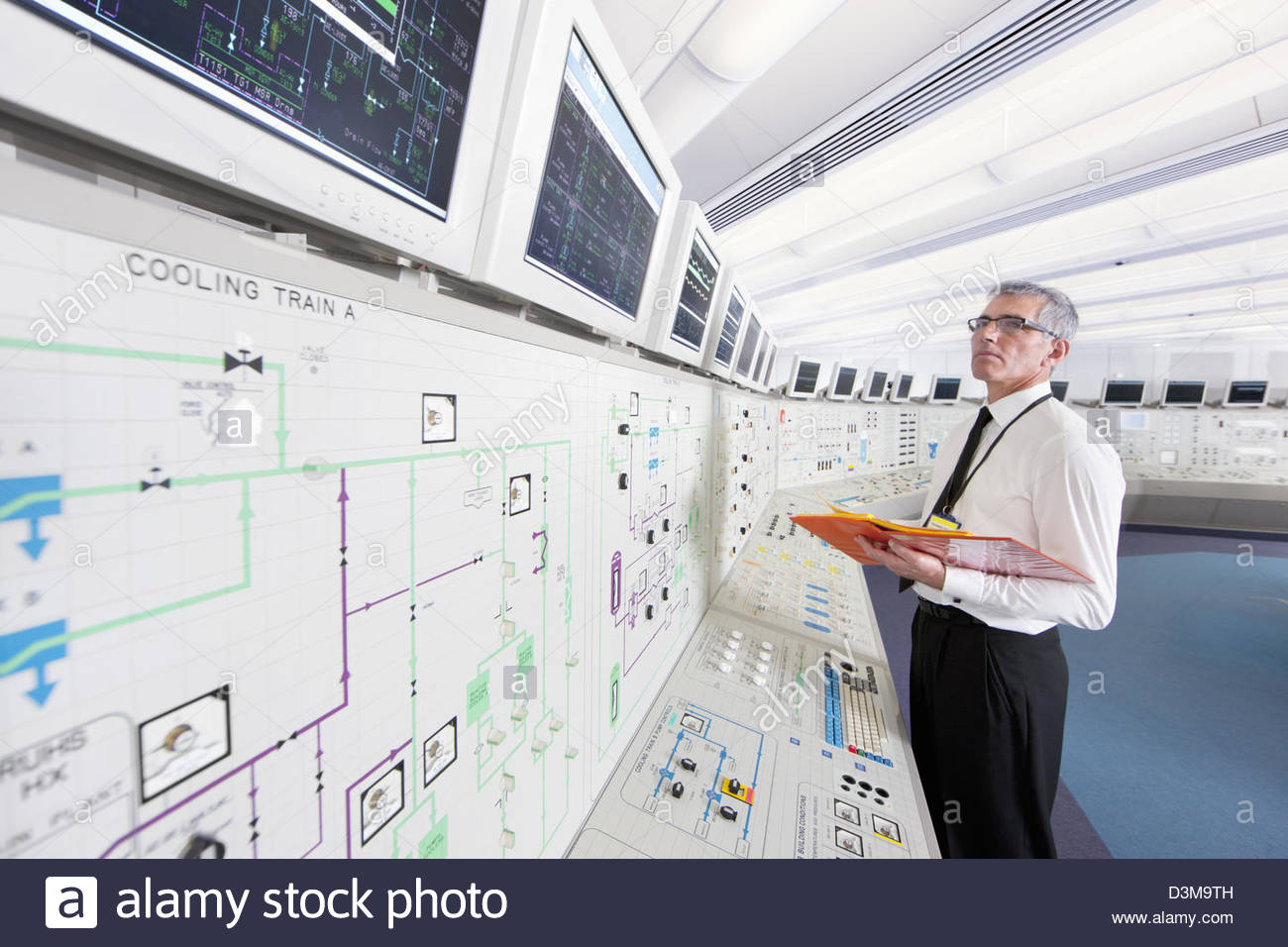 Engineer looking up at monitors in control room of nuclear power station - Stock Image