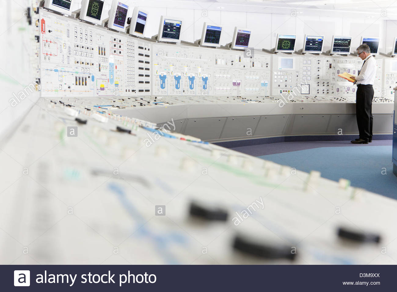Engineer working in control room of nuclear power station - Stock Image