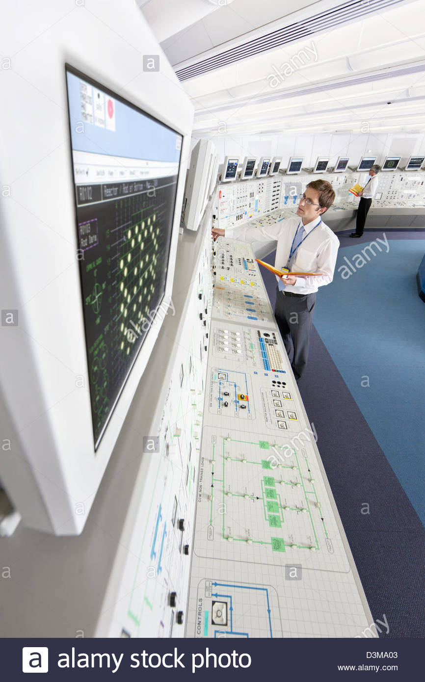 Engineer looking up at computer monitor in control room of nuclear power station - Stock Image