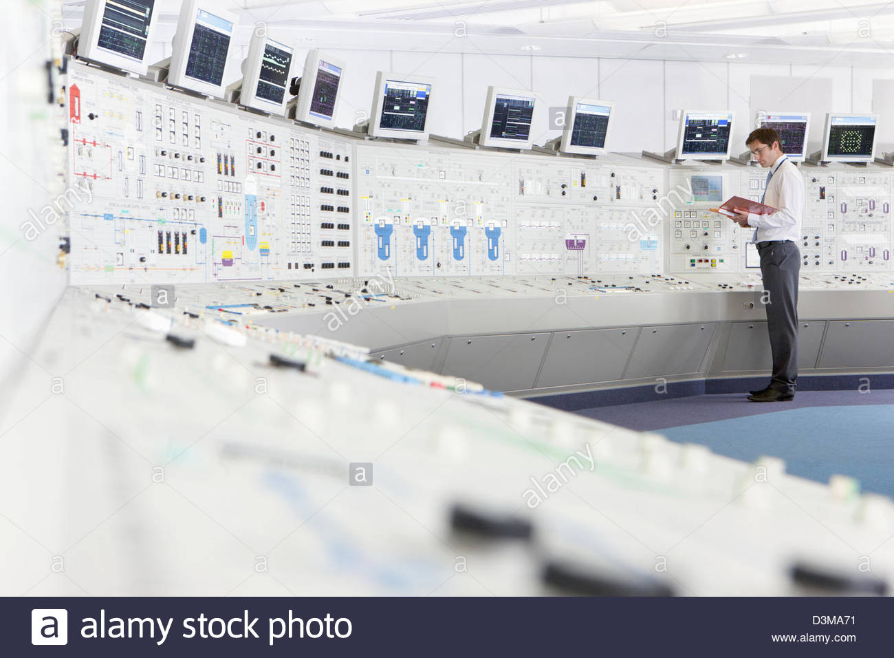 Engineer with binder at control panel in control room of nuclear power station Stock Photo