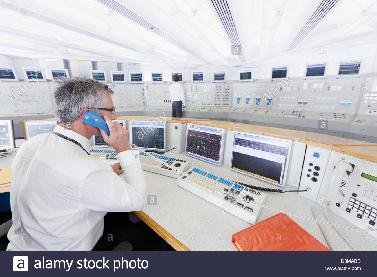 Engineer at computers in control room of nuclear power station - Stock Image