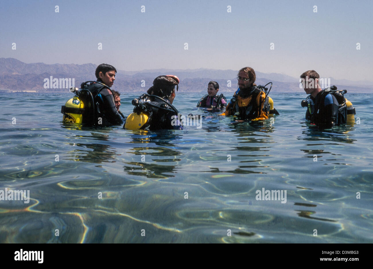 Beginners in diving instructed by the teacher. - Stock Image