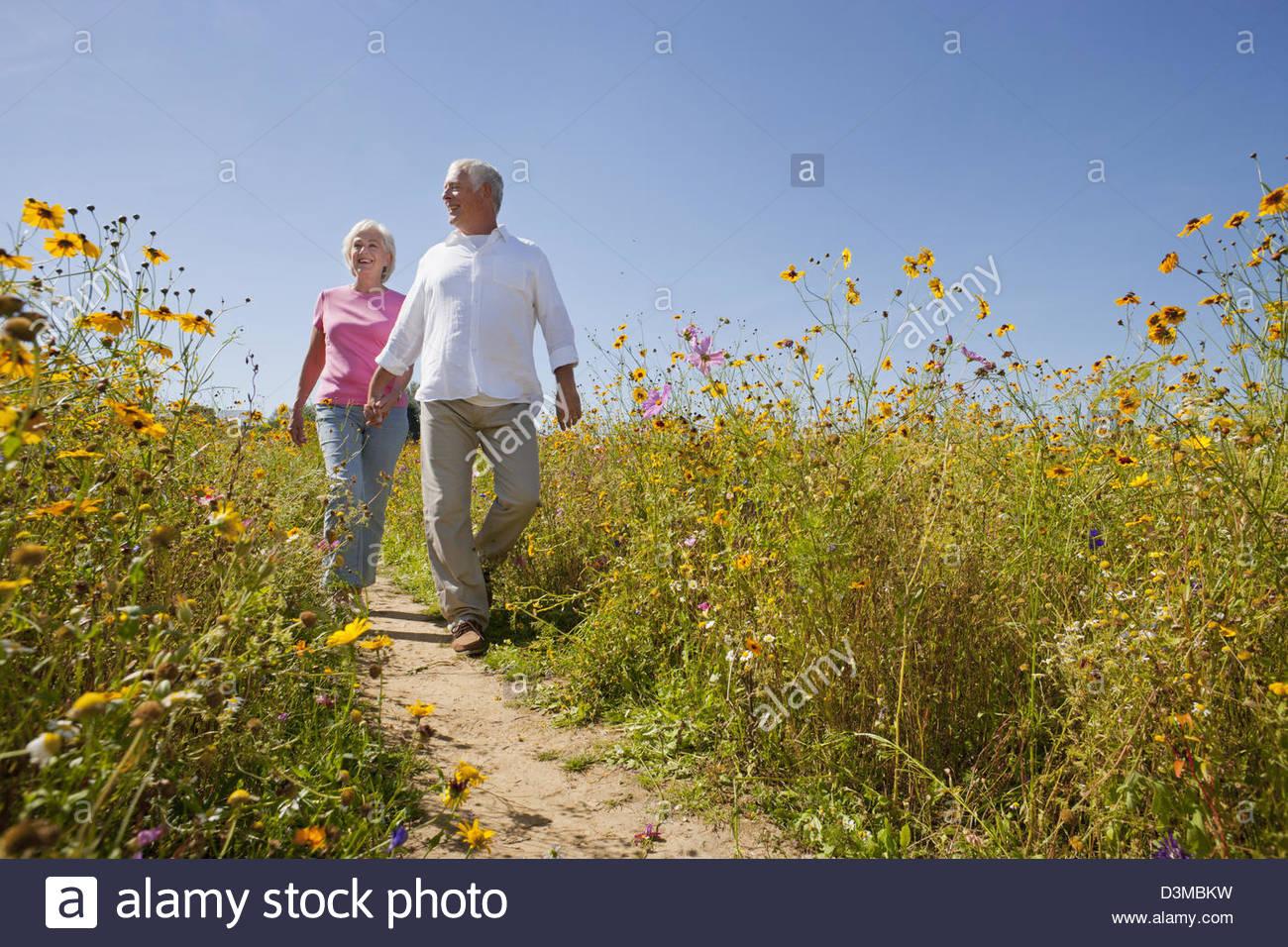Smiling senior couple walking on path through wildflower meadow Stock Photo