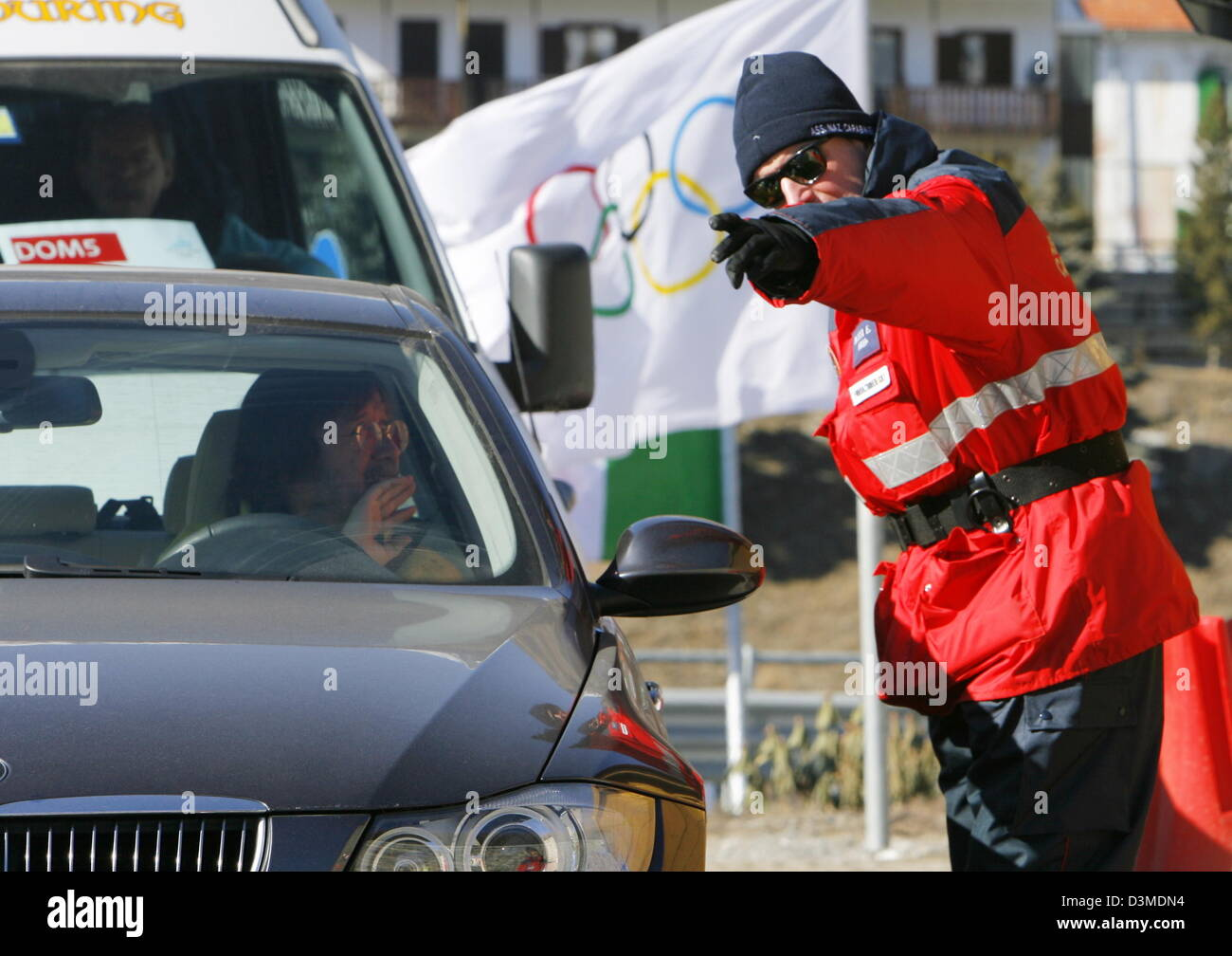 An Italian police officer stands at a traffic check point and Stock