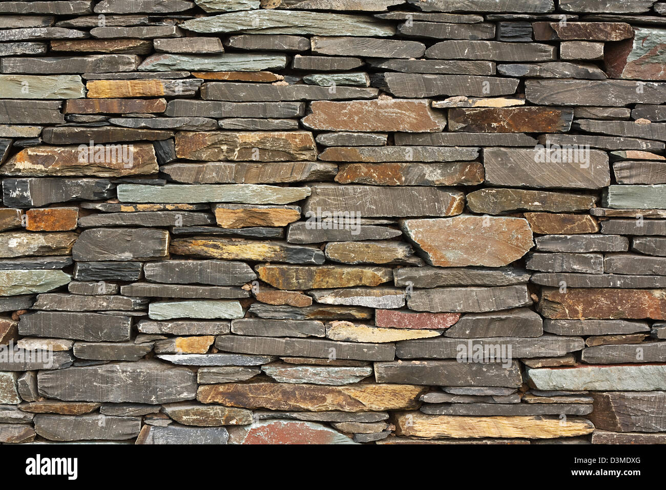 newly built dry stone wall architectural feature wall on large building good for backgrounds or wallpaper - Stock Image
