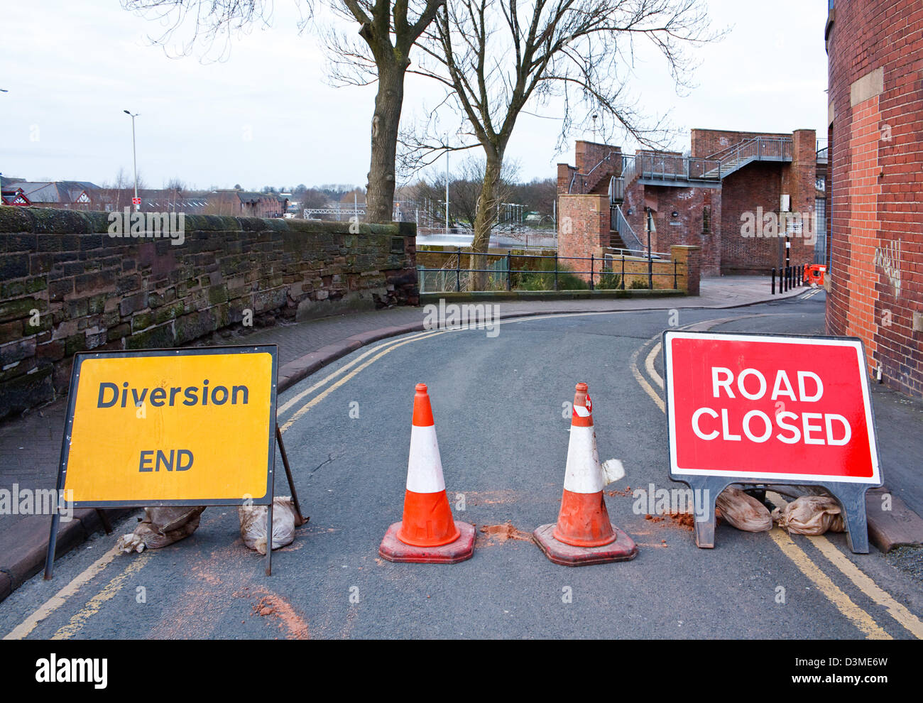 Road closed signs on a small street in the uk to stop cars and keep workmen safe - Stock Image