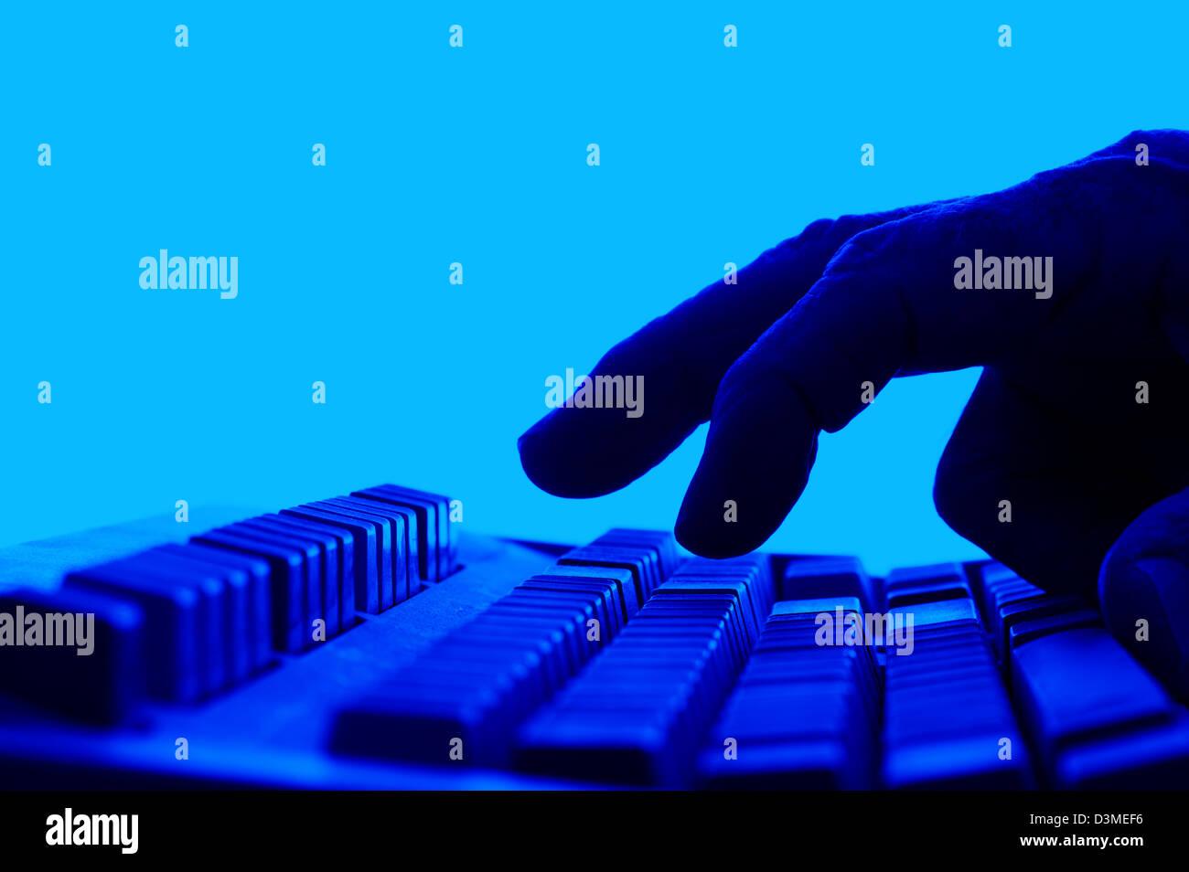 closeup fingers on keyboard blue - Stock Image