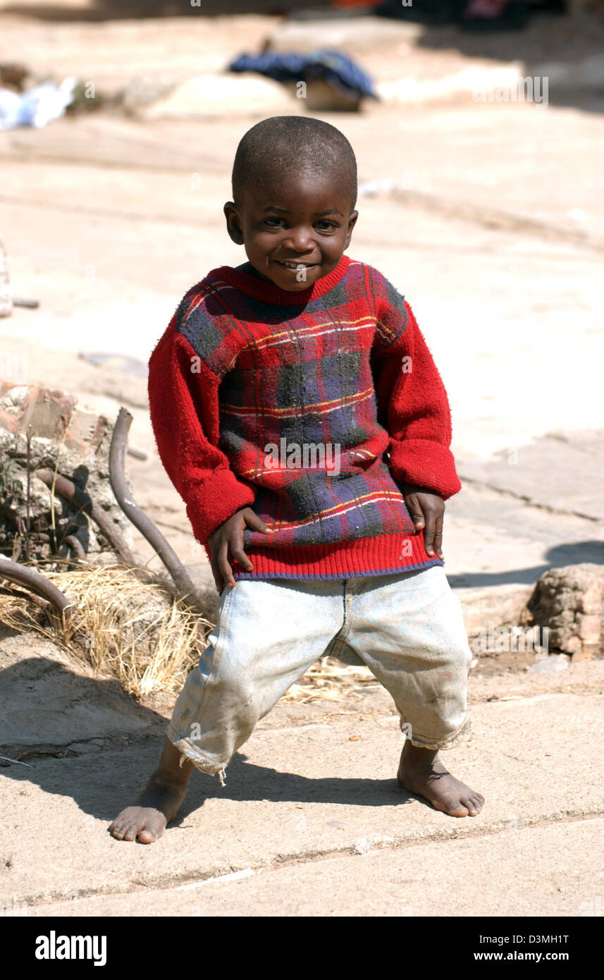 (dpa file) - A young boy stands in a dusty war-ravaged street in the province city of Huambo, Angola, 21 July 2005. - Stock Image