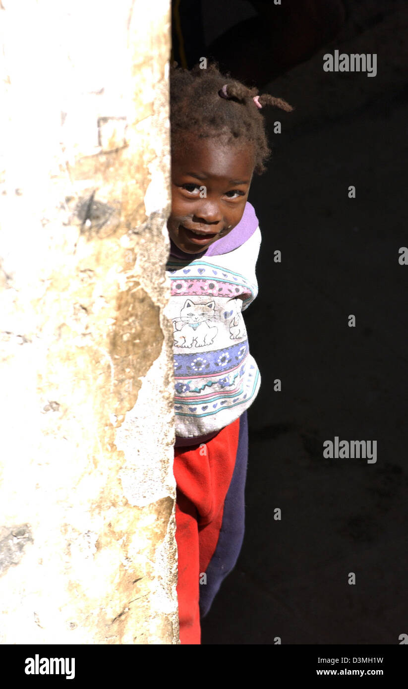 (dpa file) - A young girl lurks behind  a war-ravaged wall in the province city of Huambo, Angola, 21 July 2005. - Stock Image