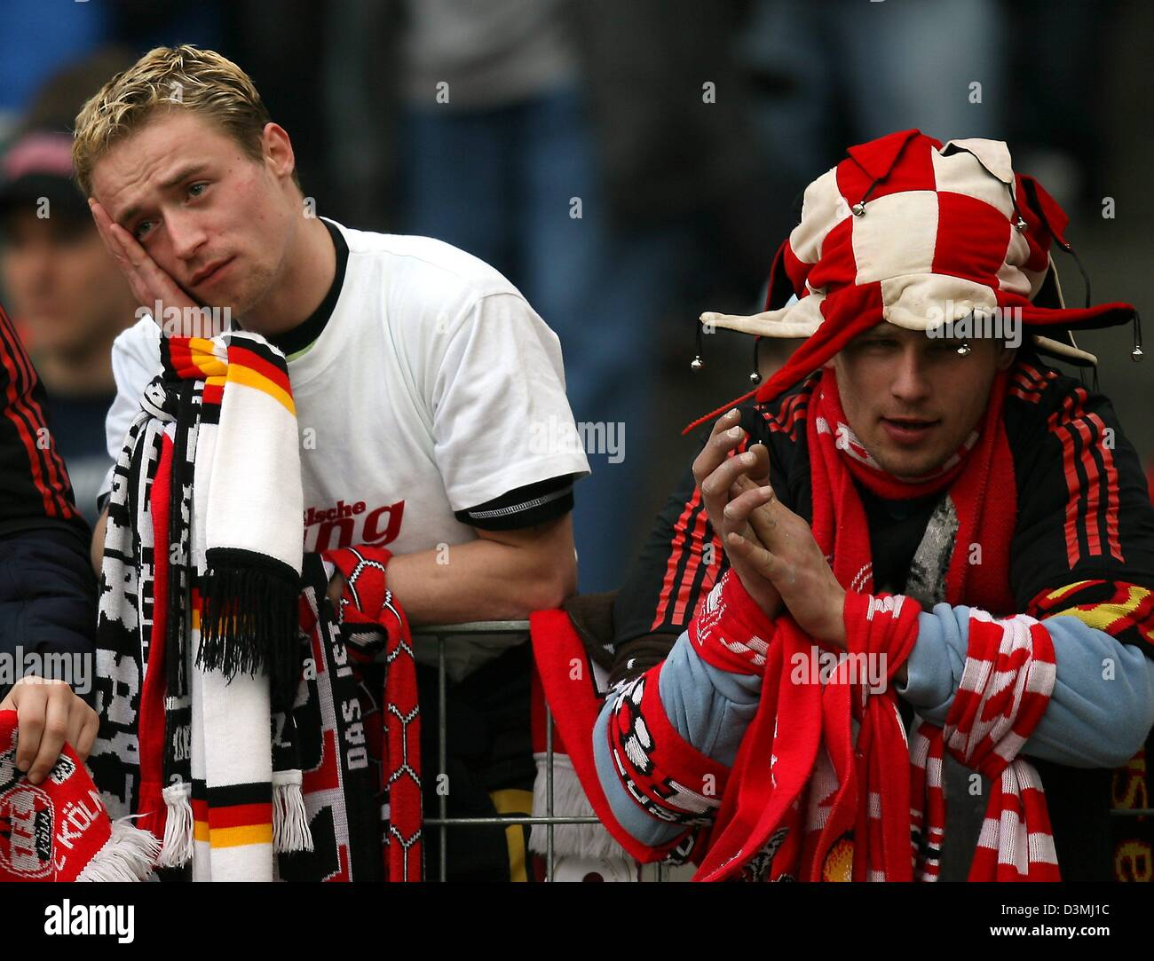 Two Cologne supporters look disappointed after the Bundesliga soccer match between 1st FC Cologne and Eintracht - Stock Image