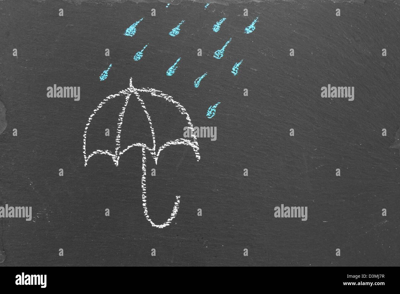 Chalk drawing of an umbrella and rain drops on slate - Stock Image