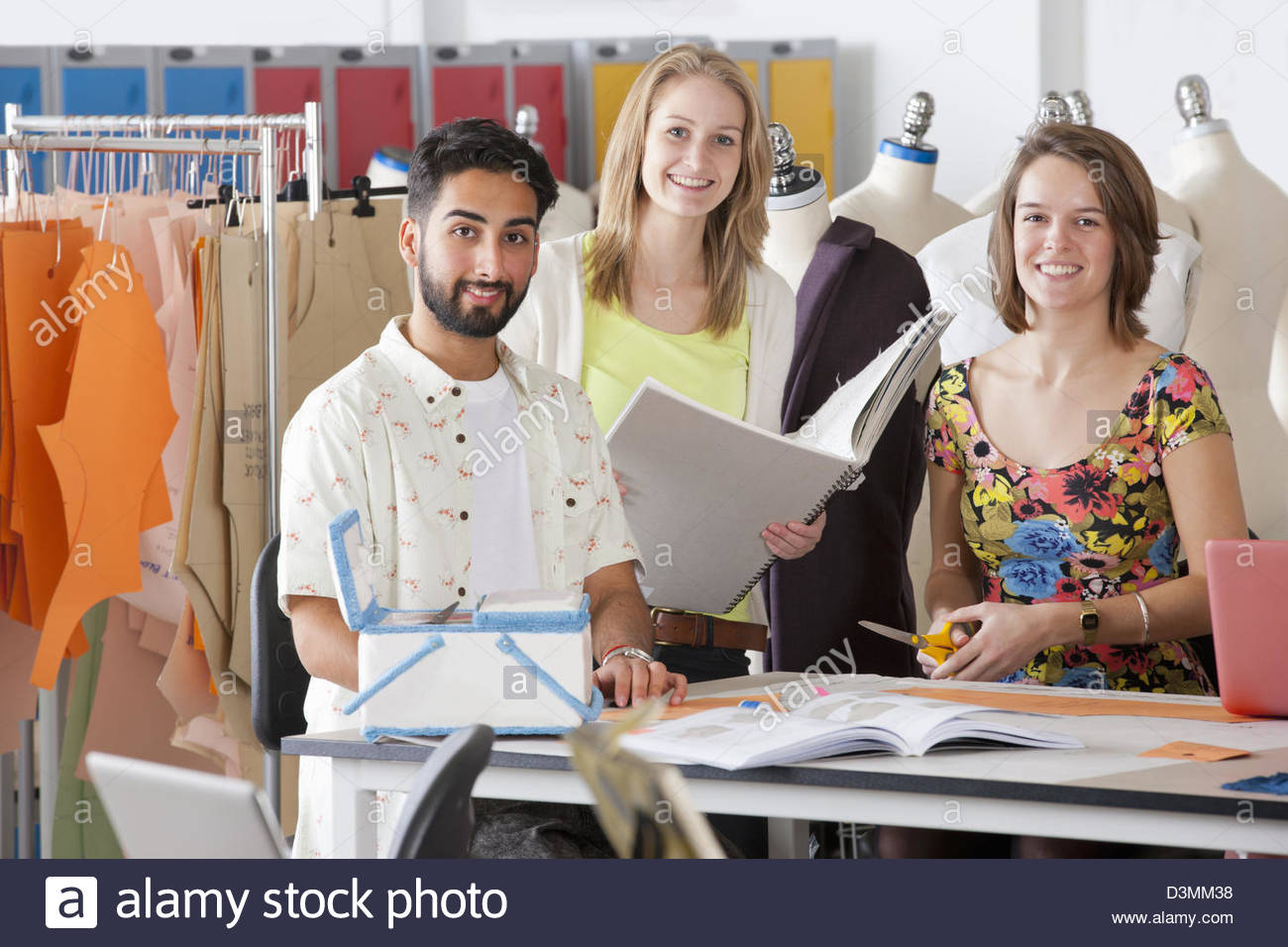 Fashion design students working together in classroom - Stock Image