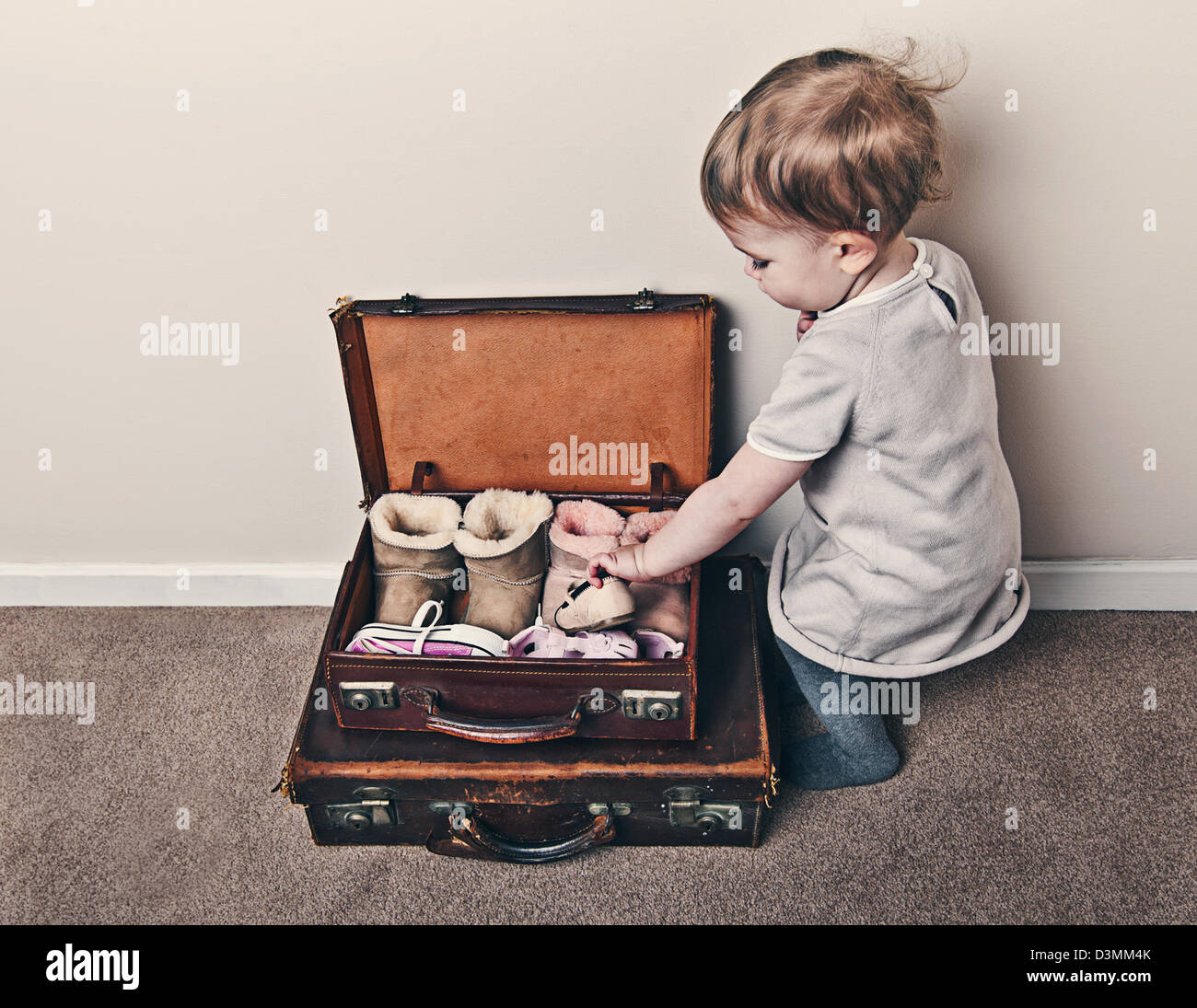 Baby Girl Packing Shoes into Case - Stock Image