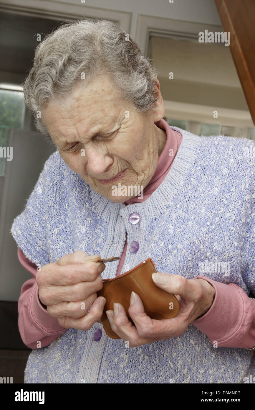 Elderly woman looking in her purse counting the pennys in the age of austerity & troubling times - Stock Image