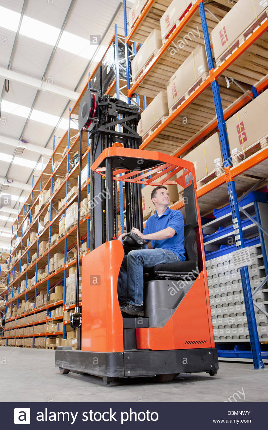 Worker operating forklift in distribution warehouse - Stock Image