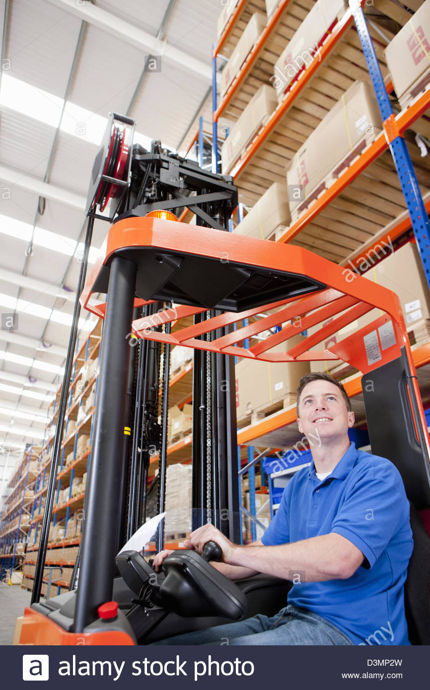 Smiling worker operating forklift in distribution warehouse - Stock Image