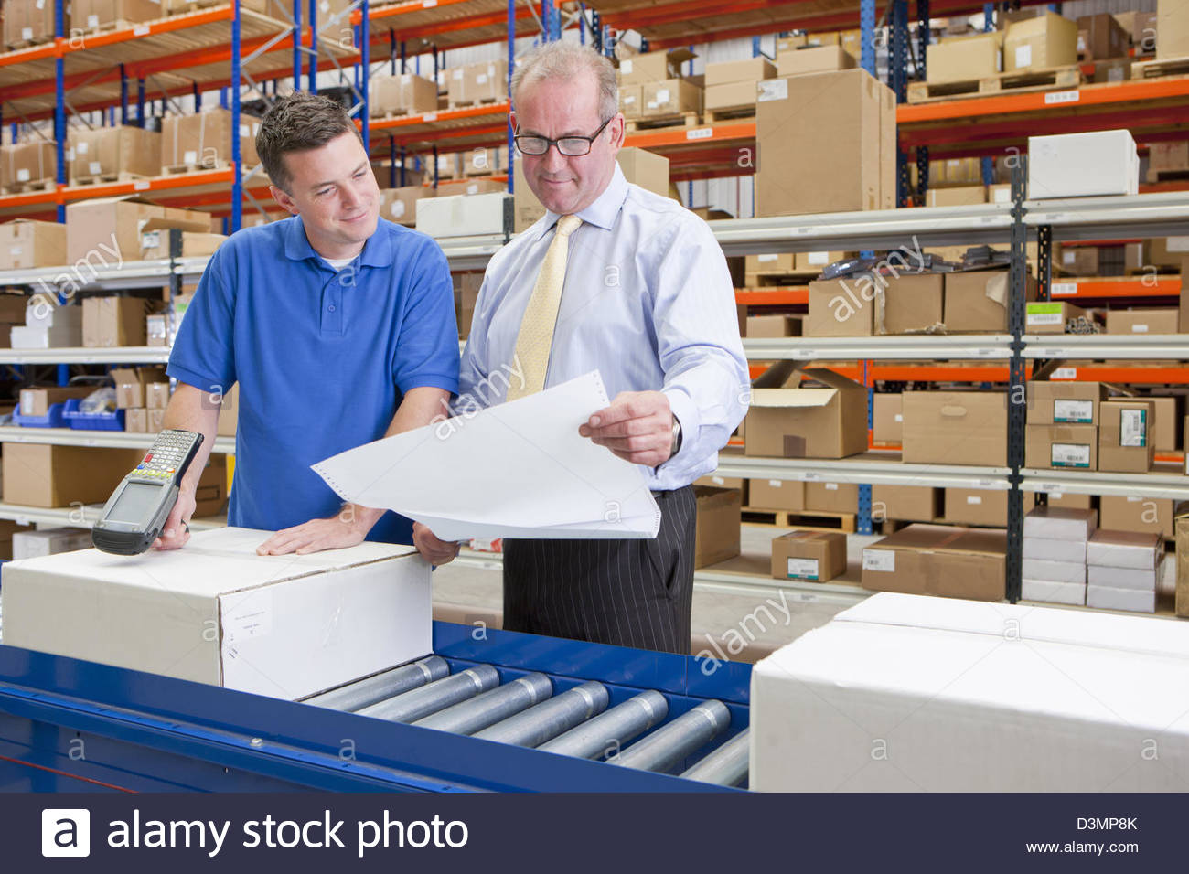 Supervisor and worker examining paperwork and scanning boxes on production line in distribution warehouse - Stock Image