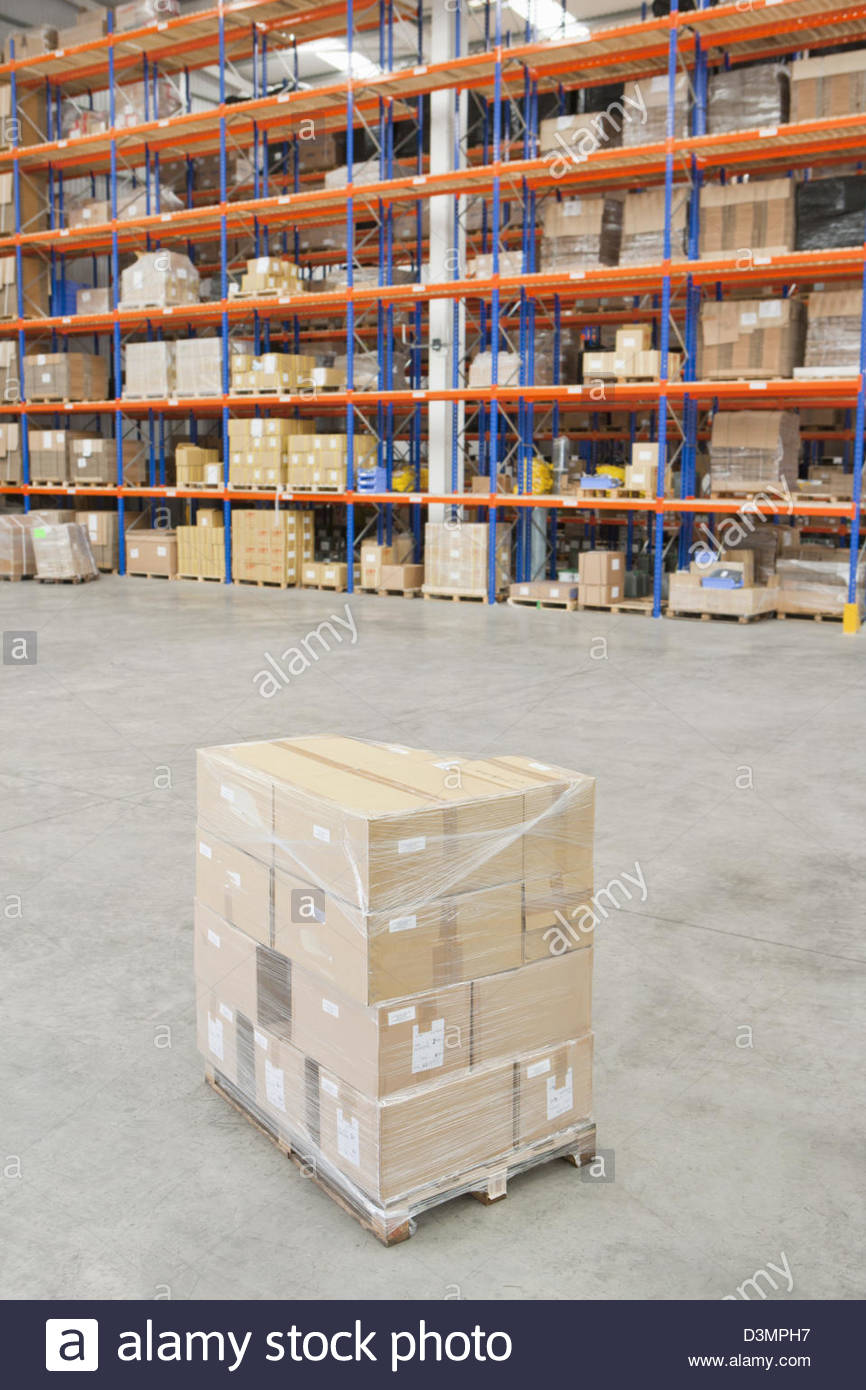 Pallet of cardboard boxes wrapped and ready in distribution warehouse - Stock Image