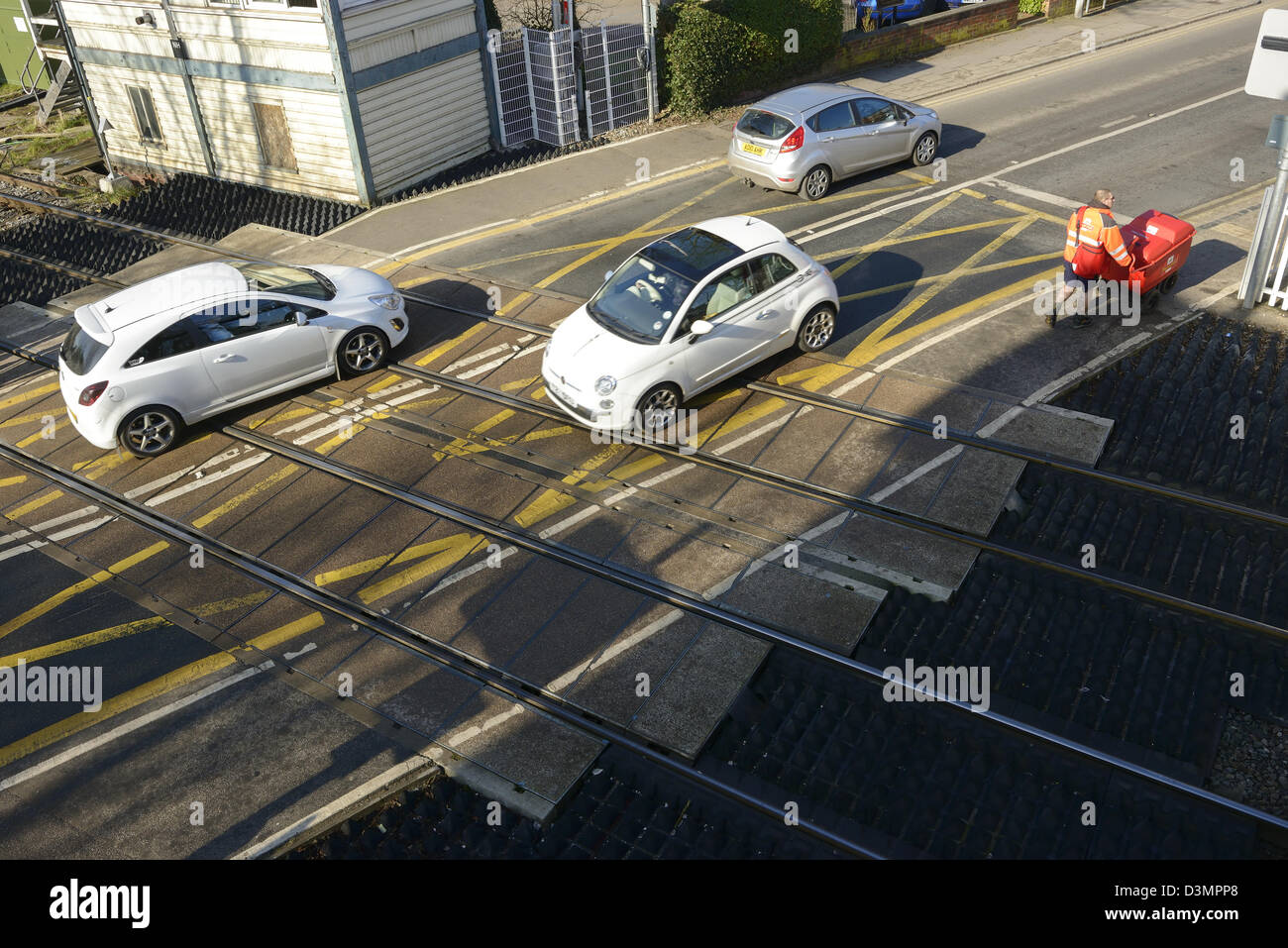 Traffic driving across the tracks of a level crossing - Stock Image