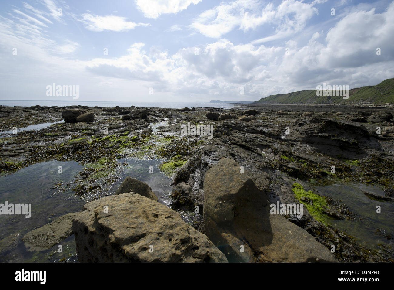 Burniston Beach on the North Yorkshire Coast overlooking North Bay and Scarborough Castle in the distance. - Stock Image