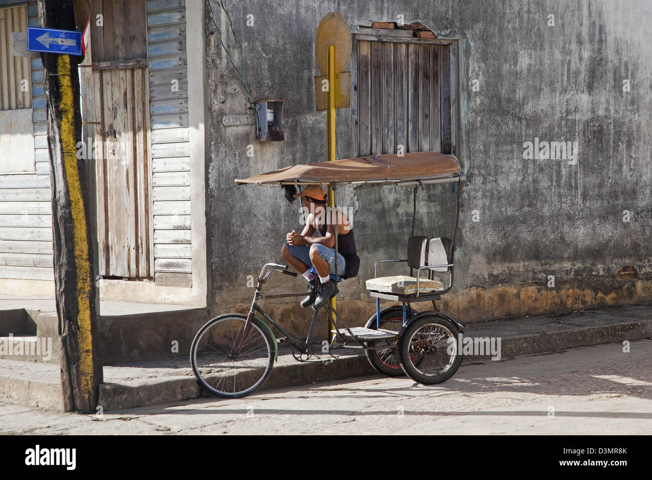 Man on three-wheeled bicycle taxi waiting for tourists in the city Baracoa, Guantánamo Province, Cuba, Caribbean - Stock Image