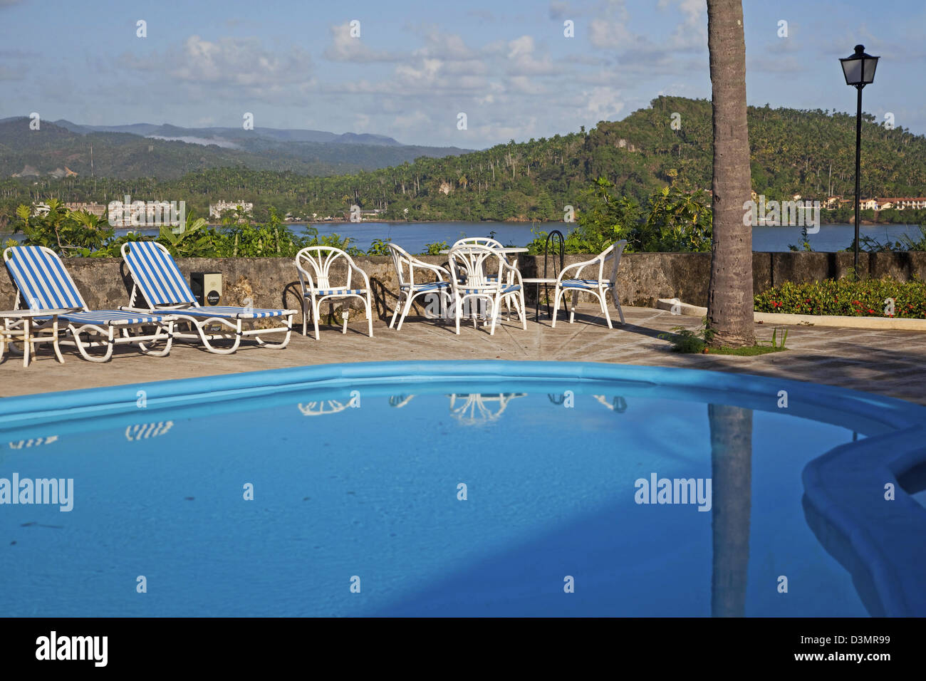 Deck chairs along blue swimming pool of Hotel El Castillo with view over bay of the Caribbean Sea at Baracoa, Cuba - Stock Image