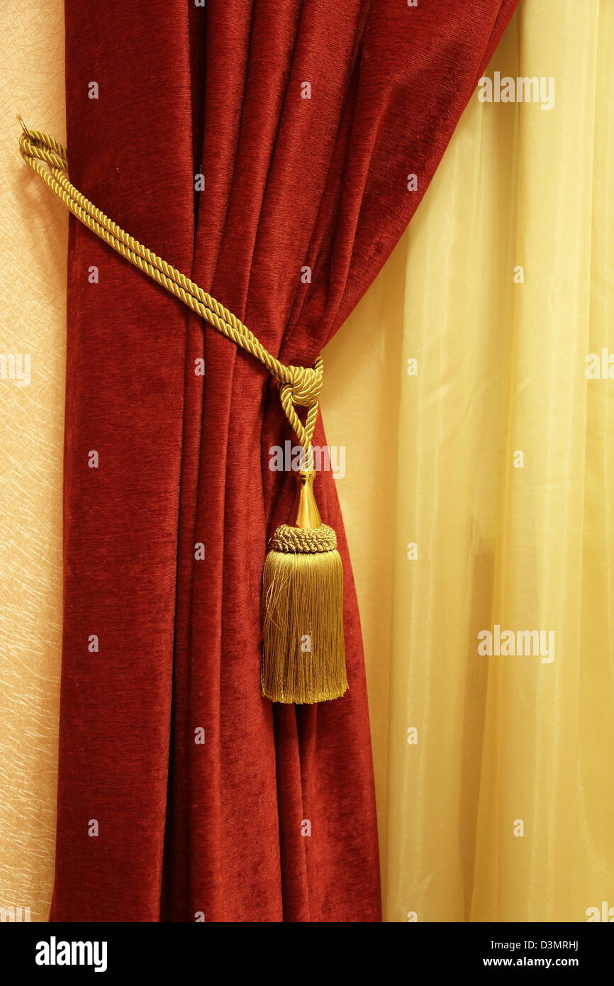 red curtain with a tassel and a rope - Stock Image