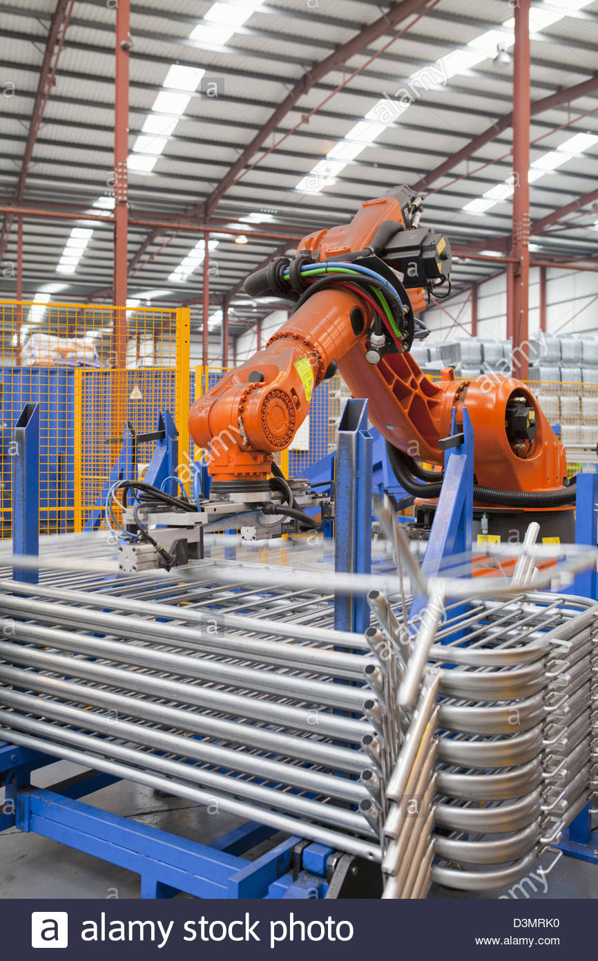 Robotic machinery lifting steel gates in factory - Stock Image