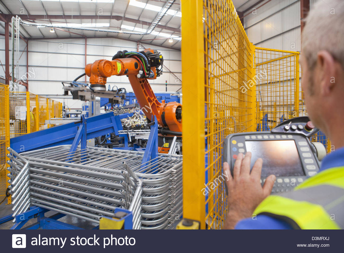 Worker operating robotic machinery in factory - Stock Image